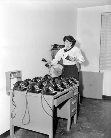 Woman trying to answer several vintage phones.